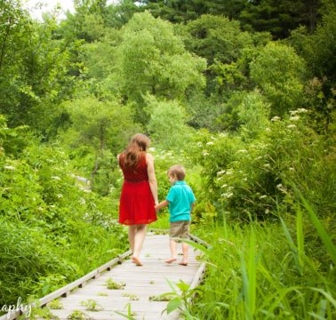 A girl in a red dress walks with a young boy in blue through lush gardens
