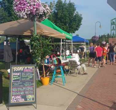 People gather at the whitewater farmers market on a sunny summer day